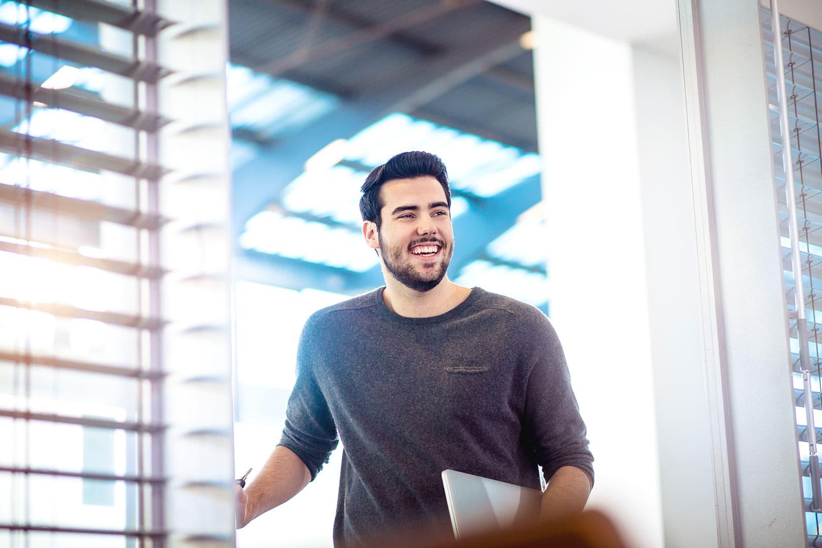lachender Mann mit Laptop betritt einen Meetingraum, fröhlich mit Zuversicht