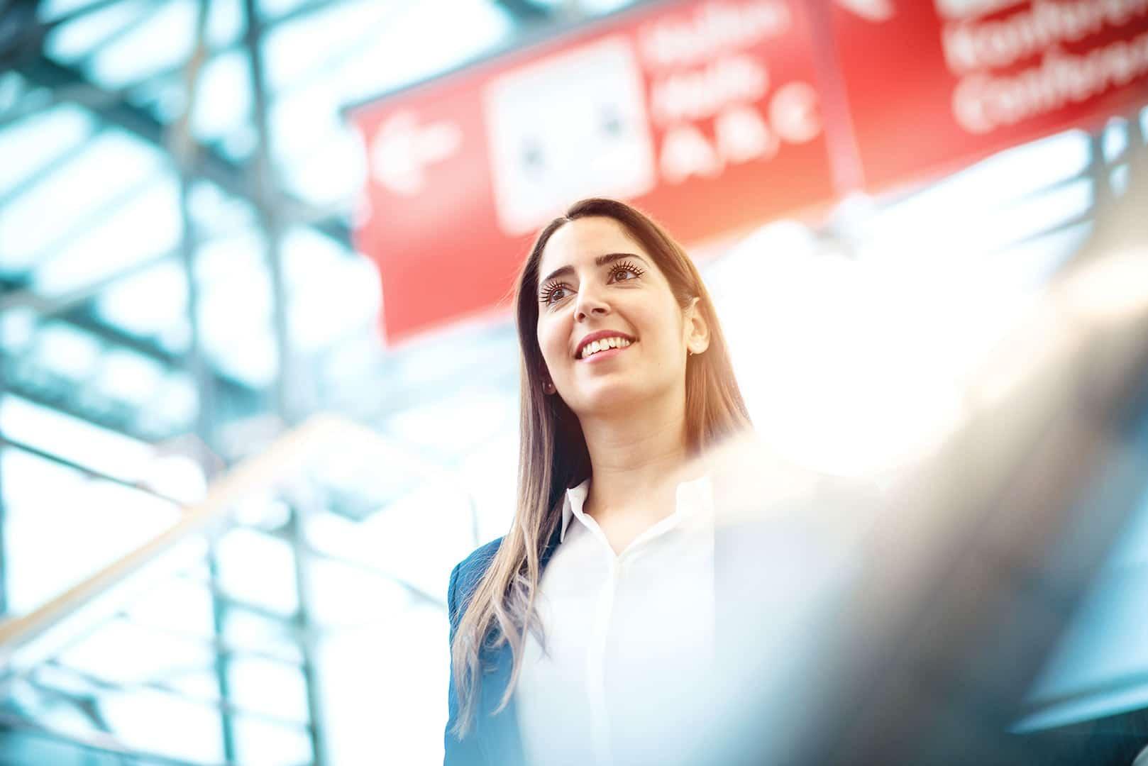 Businessfrau läuft auf einer Treppe, blickt mit Zuversicht und Freude in die Weite