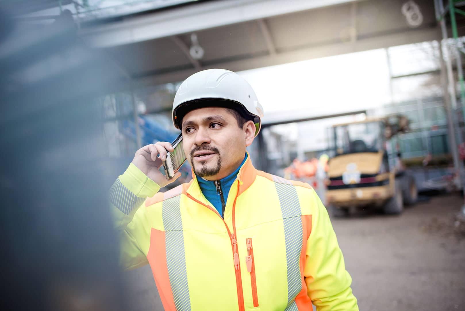 Mann mit Helm telefoniert auf einer Baustelle, Bauleiter, Bagger, Outdoor, Zuversicht, Stolz
