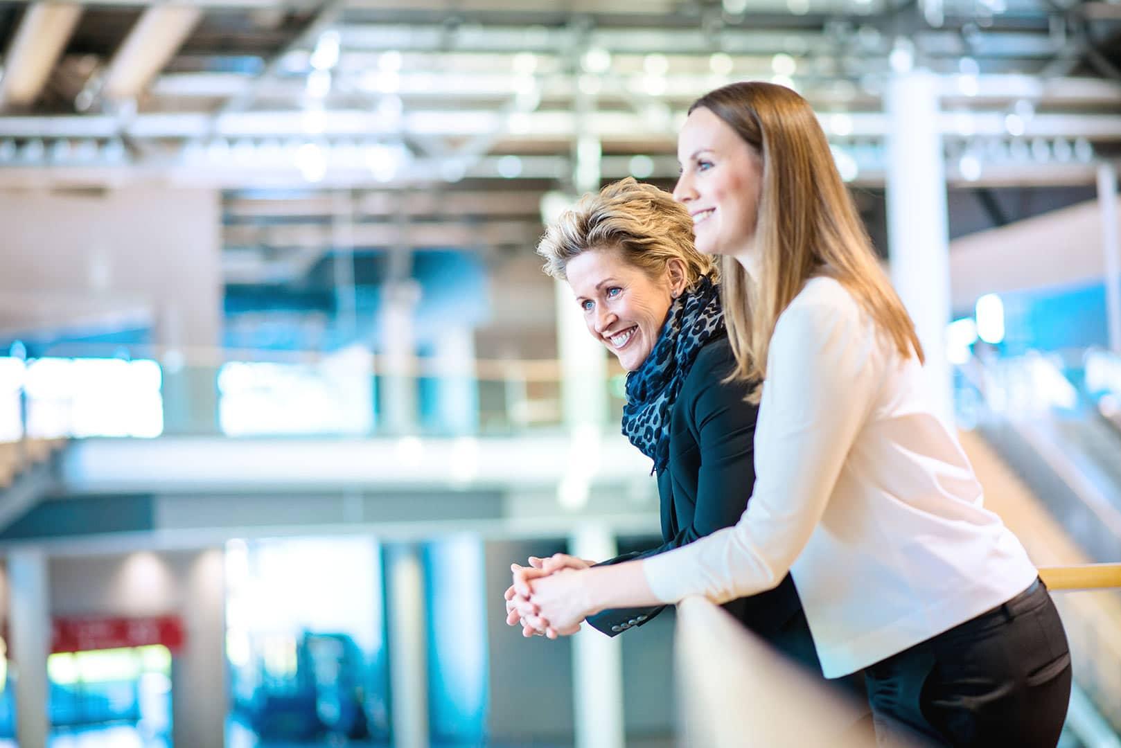 zwei Frau lachen bei einer Besprechung in einer Halle, zuversichtlich, hell, freundlich