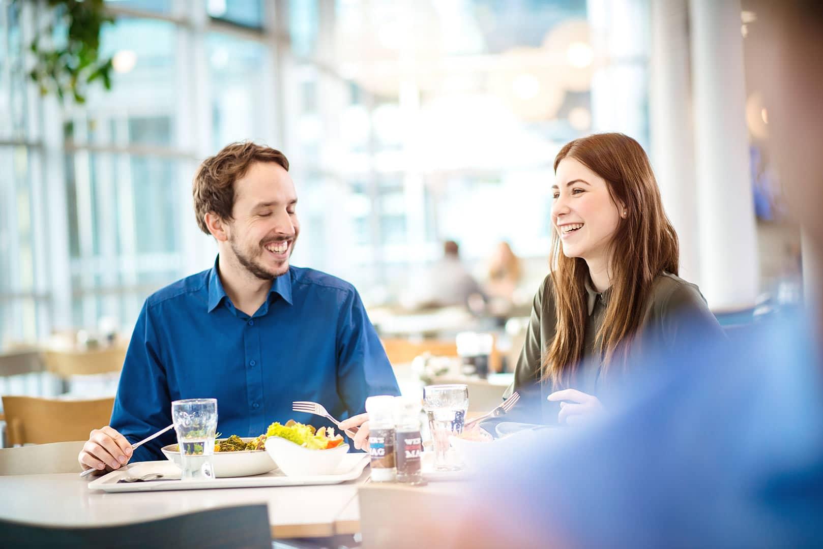 fröhliche Mitarbeiter bei Essen in einer Kantine, lachend