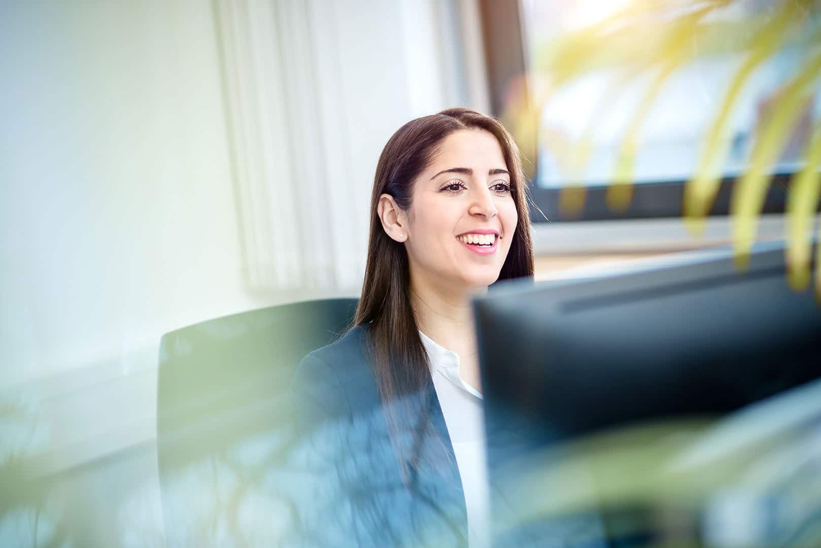 lachende Mitarbeiterin am Computer im Büro, fröhlich, sonnig