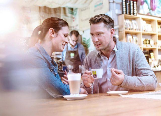 Mann und Frau trinken Kaffee in einer Bar, Espresso, Cappuccino, fröhlich und entspannt, Tasse, Kaffeerösterei