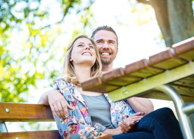glückliches Paar im Park, sitzen, geniessen die Sonne, Grün, Bäume, verliebt, kuscheln