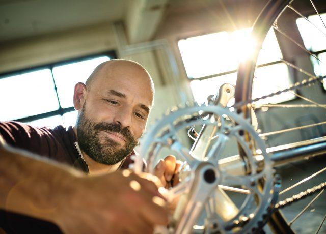 Mann arbeitet an einem Vintage Rennrad, sonnige Atmosphäre, Lensflare, Retrostyle, Gegenlicht, Loft