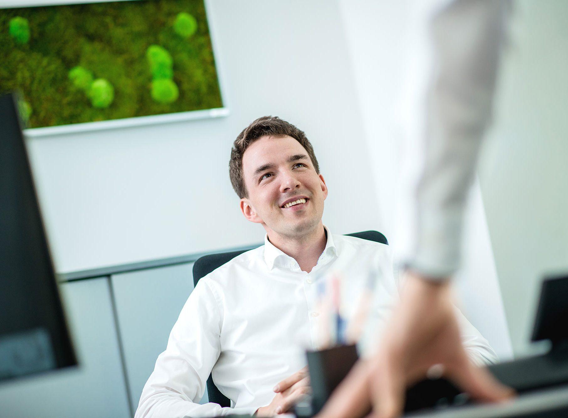 Mann am Schreibtisch zufrieden glücklich selbstbewusst