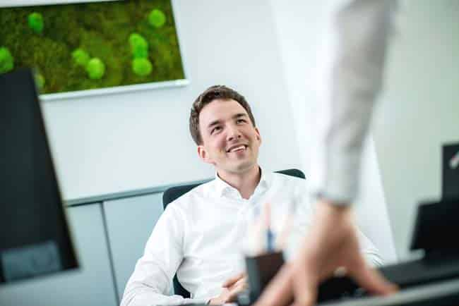 Mann zuversichtlich am Schreibtisch im Office Meeting Besprechung hell Freude Businessfotografie