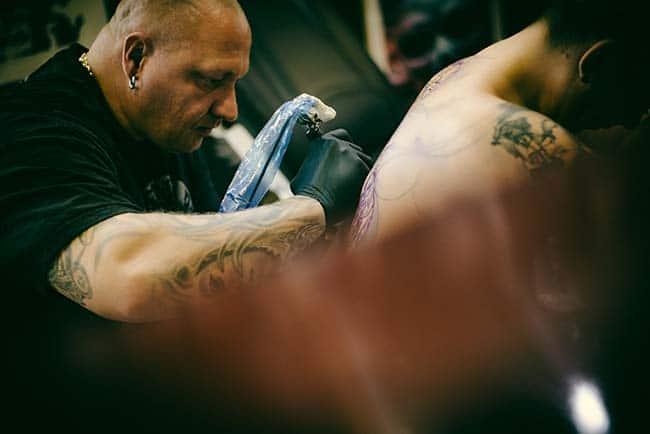Tattoo Artist bei der Arbeit im Tattoostudio Mann Frau Muskeln dunkel konzentriert