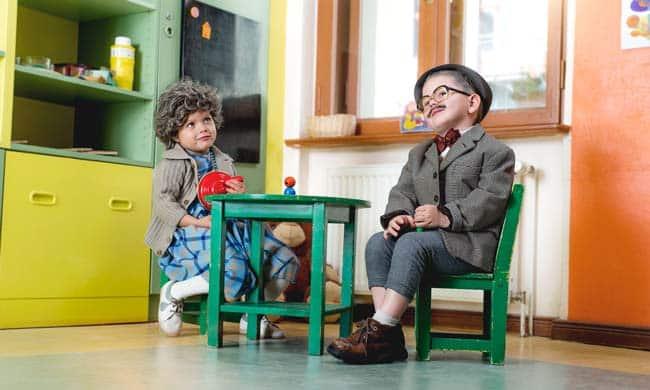 Kinder an Tisch im Kindergarten verkleidet Werbefotografie Kinderfotografie Freude bunt