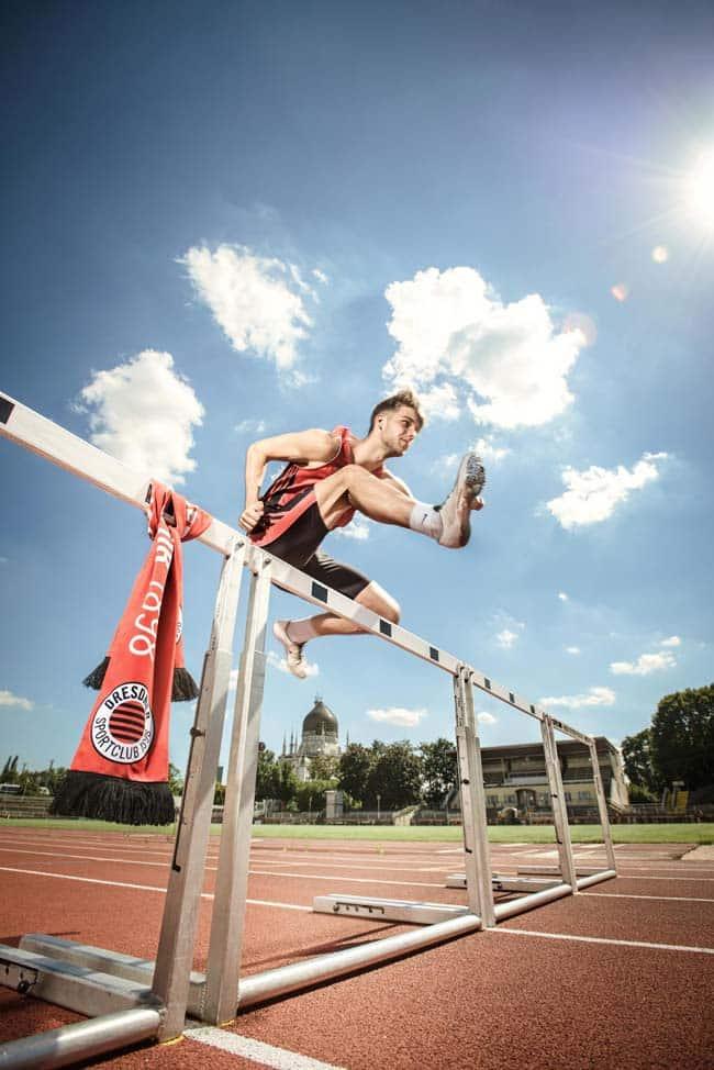 Sportler beim Hürdenlauf Sonne energisch Energie Sportfotografie Werbefotografie Dresden Ostra Gehege
