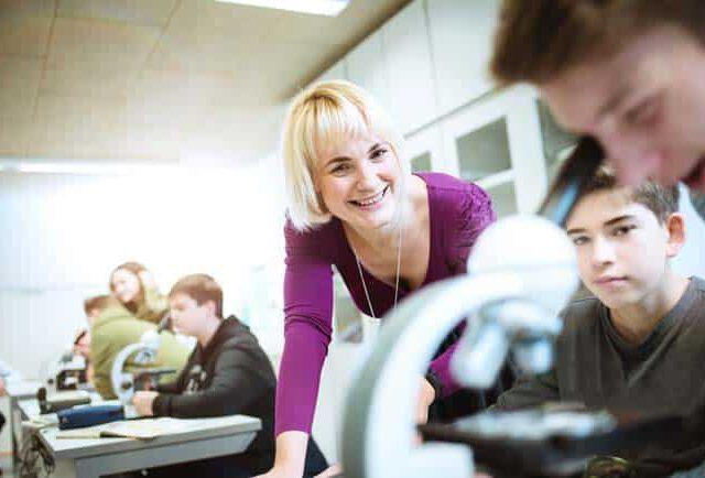 Lehrerin mit Schülern in Biologie Unterricht Freude entspannt Schule lernen