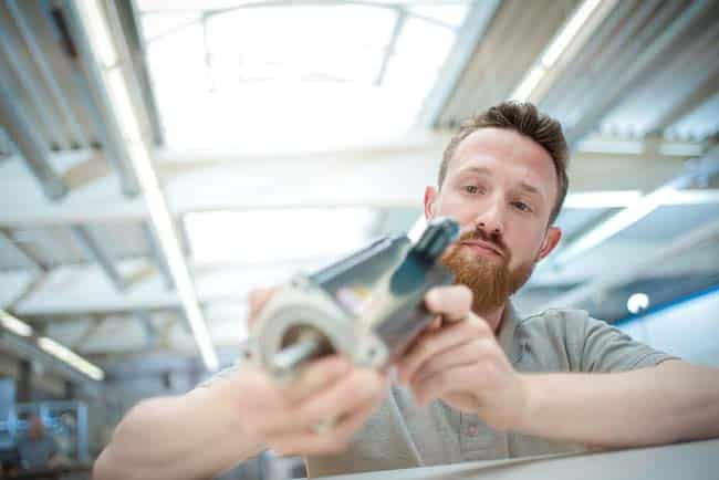 Mann in Fertigungshalle mit Motor in der Hand prüfend hell Unternehmensfotografie Industriefotografie