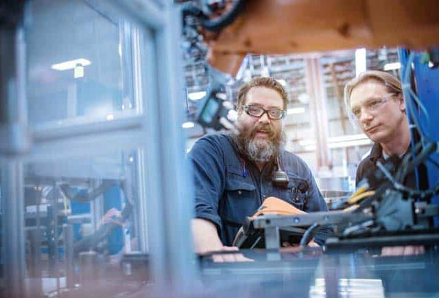 Ingenieur und Arbeiter an Roboter in Fertigungshalle Besprechung Hightech Technologie