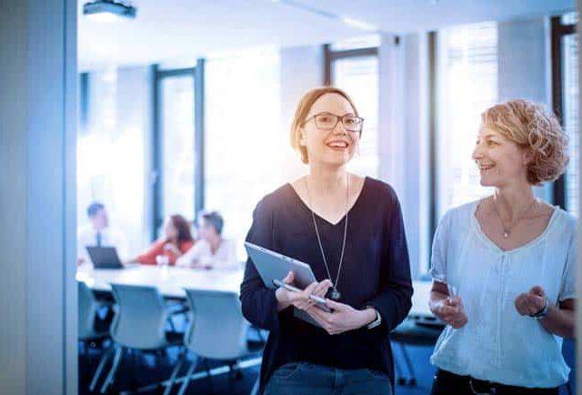 Zwei Frauen in Büro Umfeld Meetingraum Unterlagen Freude Zuversicht hell leuchtend