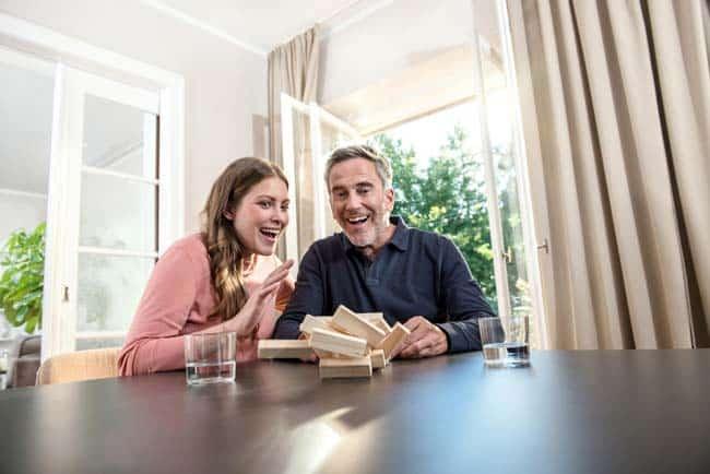 Mann und Frau spielen Jenga am Tisch voller Freude Überraschung sonnig Werbekampagne Lifestyle