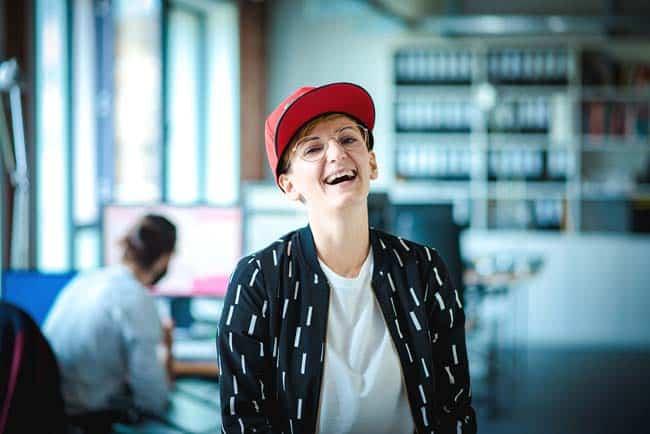 lachende Frau mit Cap in Büro Office sonnig Lifestyle Schreibtisch Loft