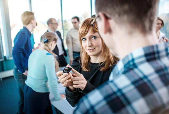 Frau bei Besprechung in Meetingraum mit Elektro Bauteil in der Hand