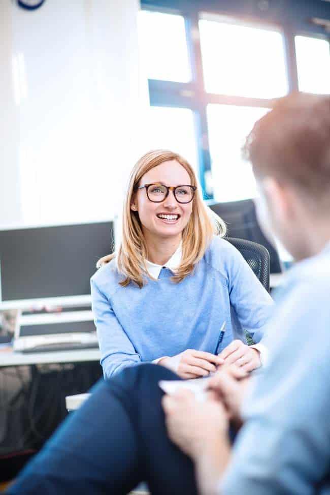 Frau mit Brille im Office Meeting hell leuchtend Sonne lachend Freude Zuversicht