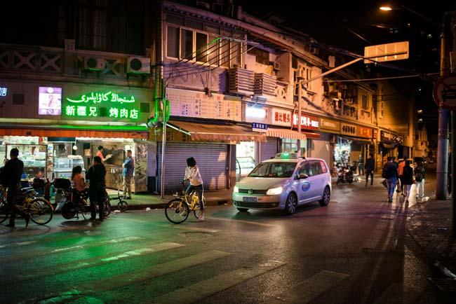 Nacht in Shanghai Strassenszene Taxi Fahrrad Leuchtreklame Streetphotography