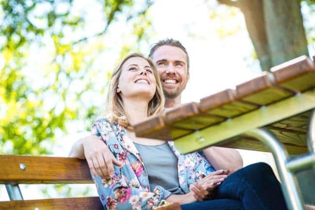 Junges Paar entspannt auf Parkbank lachen verliebt kuscheln Sonne Werbefotografie Lifestylefotografie Lifestyle