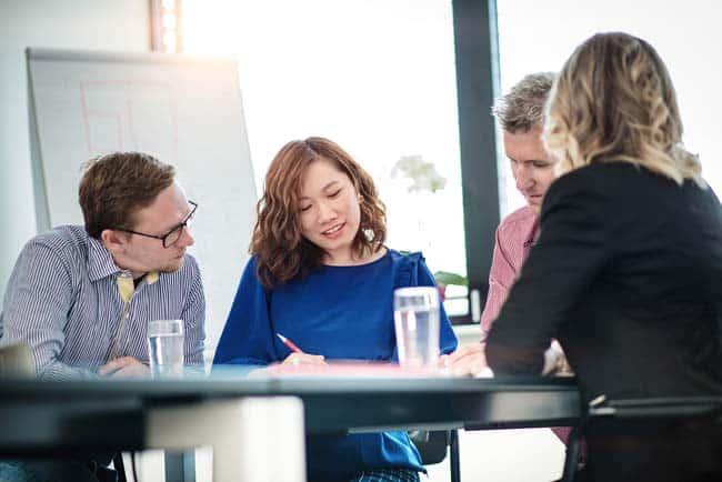 Business Gruppe bei Besprechung am Tisch sonnig hell Freude konzentriert Meetingraum Flipchart Businessfotografie Unternehmensfotografie