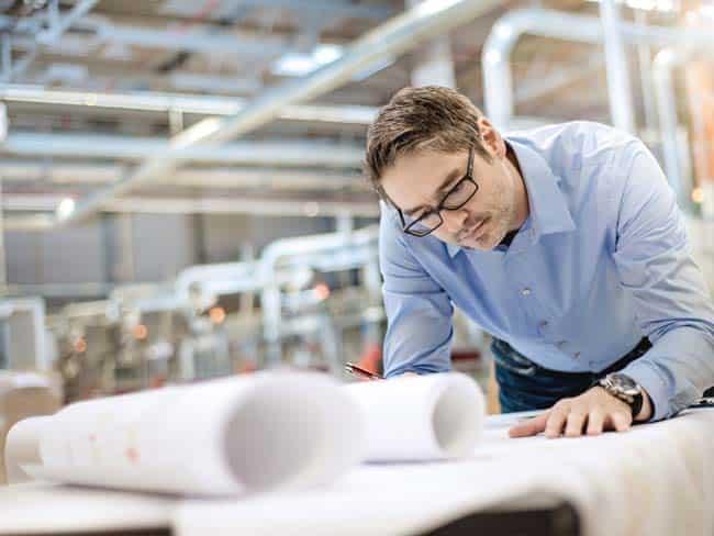 Ingenieur mit Plänen in Industriehalle konzentriert Hightech Industriefotografie Unternehmensfotografie