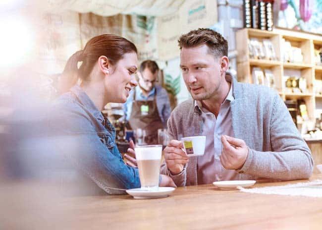 Mann und Frau trinken Kaffee geniessen lachen Freude Cappuccino Espresso Kaffeerösterei