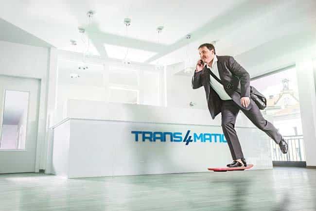 Business Mann mit Handy auf Hoverboard in Büro Umgebung