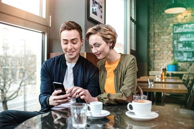 Junges Paar sitzt im Cafe innig verliebt vertraut mit Smartphone Tisch Tassen Kaffee Lifestyle Reise