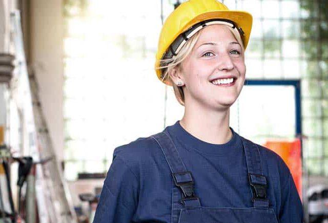 junge Frau in Industrie Werkstatt Blaumann Helm sonnig Freude Energie Werkzeug