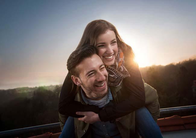 Junges Paar im Sonnenaufgang voller Freude Liebe verliebt blaue Stunde Lachen