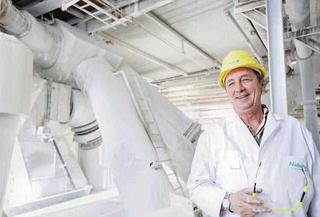 Industriefotografie Mann in Industriehalle Arbeiter Helm Kittel weiß Unternehmensfotografie