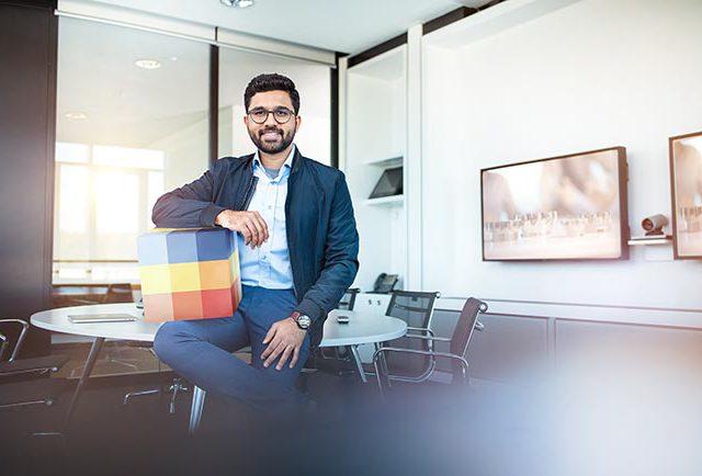 SECO TOOLS Employer Branding Kampagne Mann in Casual Business sitzt in Meetingraum und schaut zuversichtlich und freundlich