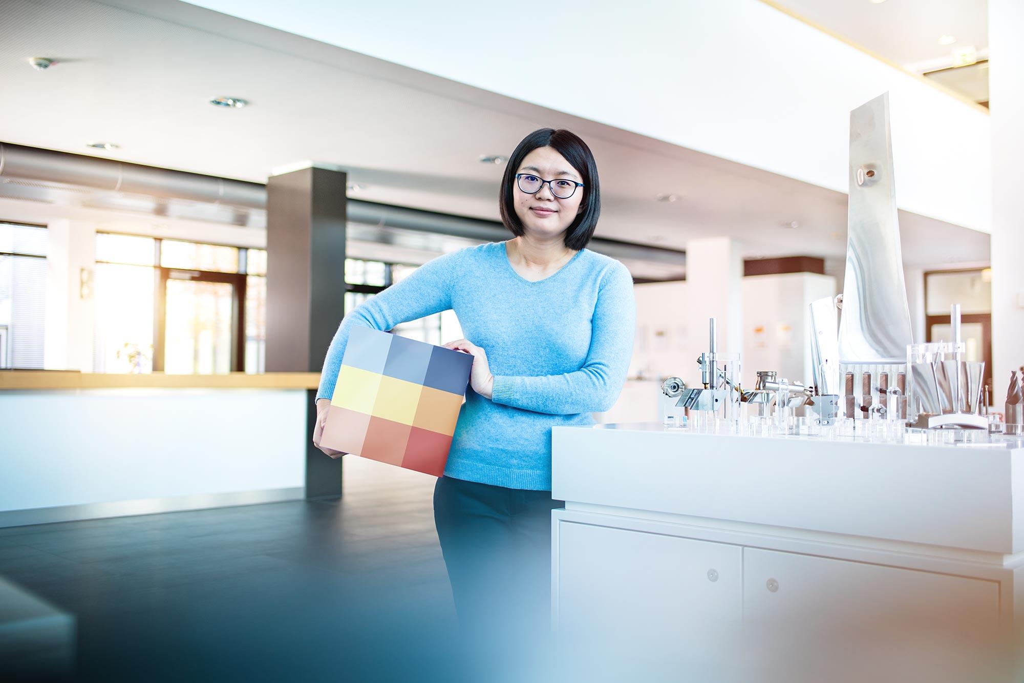 SECO TOOLS Employer Branding Kampagne Junge asiatische Frau steht im Empfangsbereich an Display für CNC Produkte