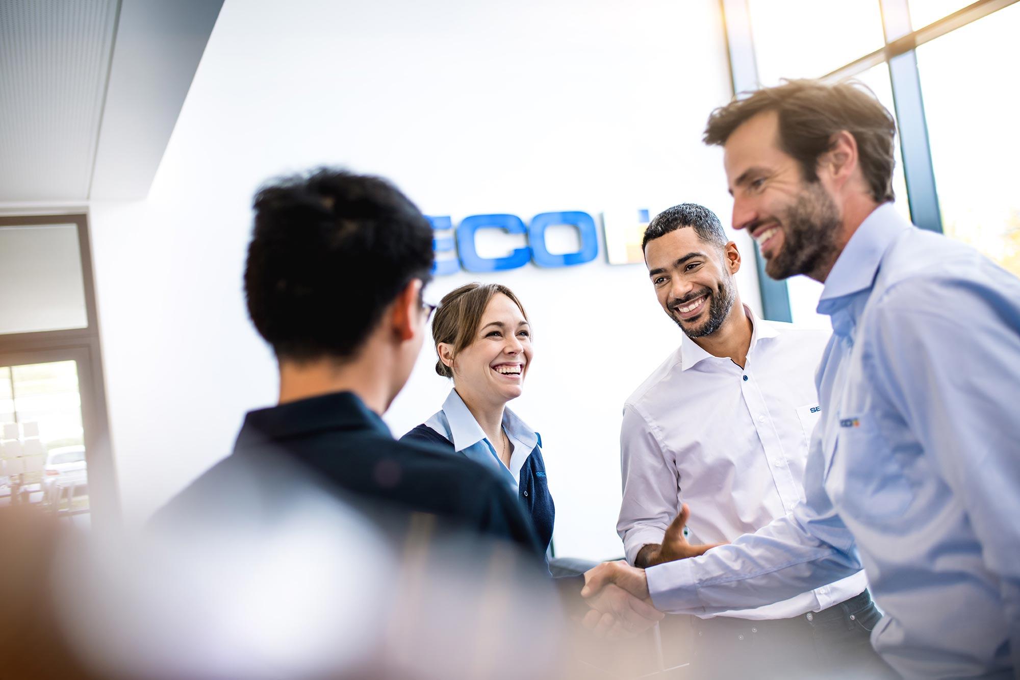 SECO-TOOLS Global Communication Handshake zwischen freundlichen Mitarbeitern und Kunden im Foyer Lachen Positive Energie Business Mann und Frau