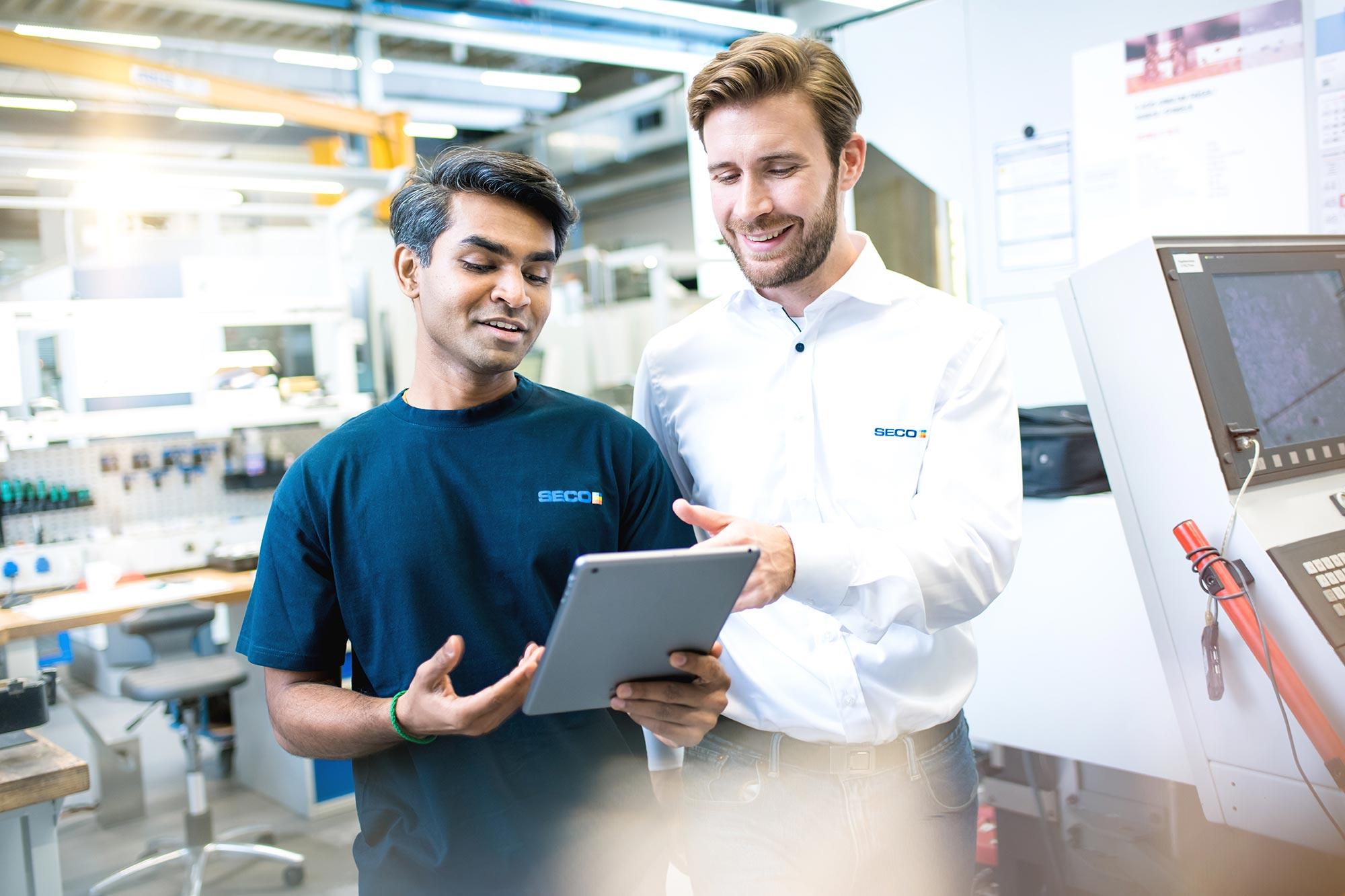 SECO-TOOLS-Global Communication Mitarbeiter der Produktion und Kunde sprechen konzentriert mit Tablet in der Hand vor CNC Maschine