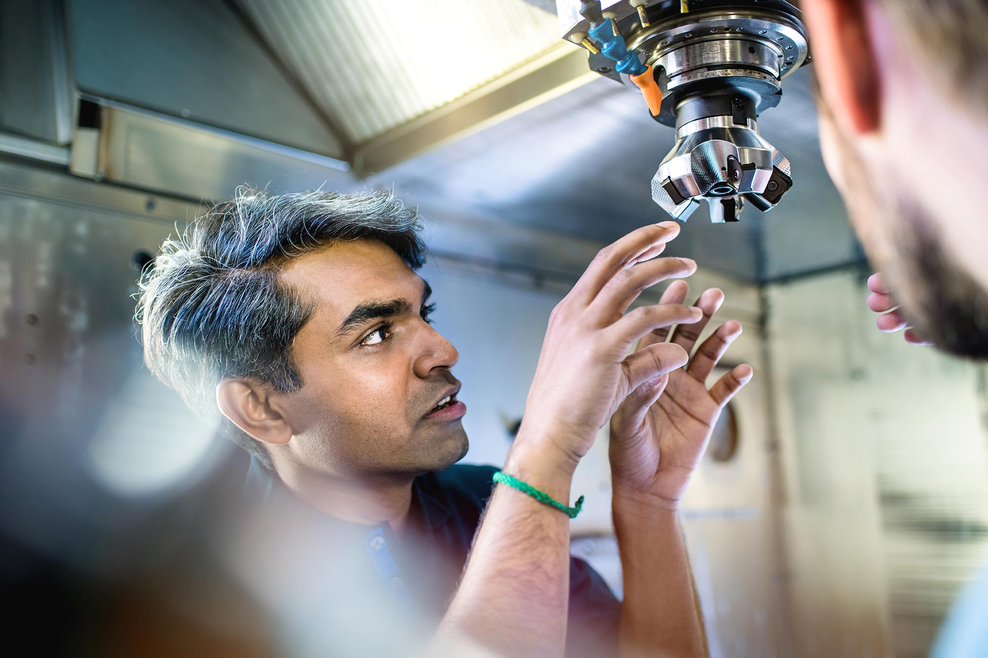 SECO-TOOLS-Global Communication Mitarbeiter der Produktion und Kunde sprechen konzentriert mit Werkzeug in der CNC Maschine