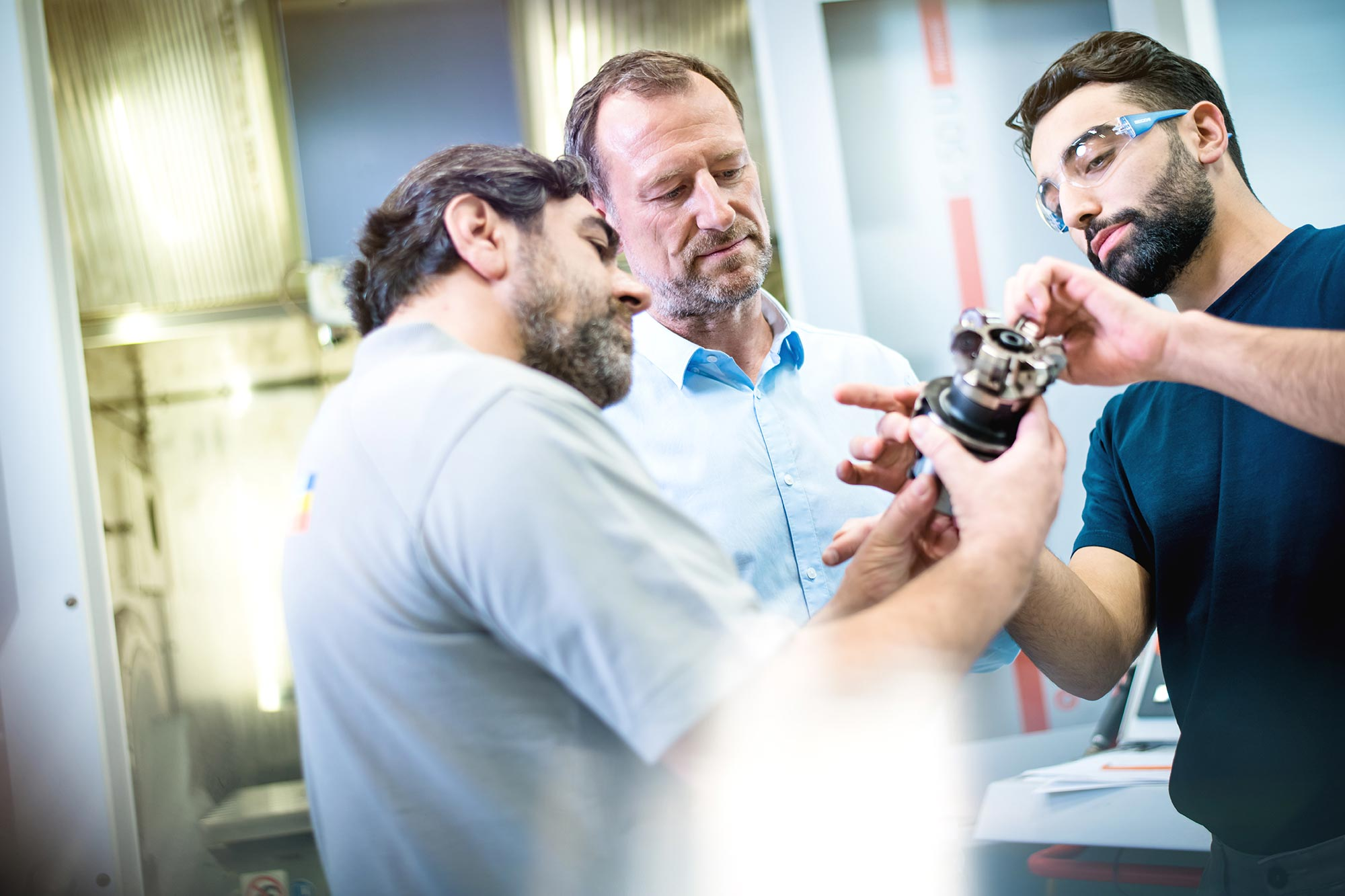 SECO-TOOLS-Global Communication Mitarbeiter der Produktion und Kunde sprechen konzentriert mit Werkzeug in der Hand vor CNC Maschine