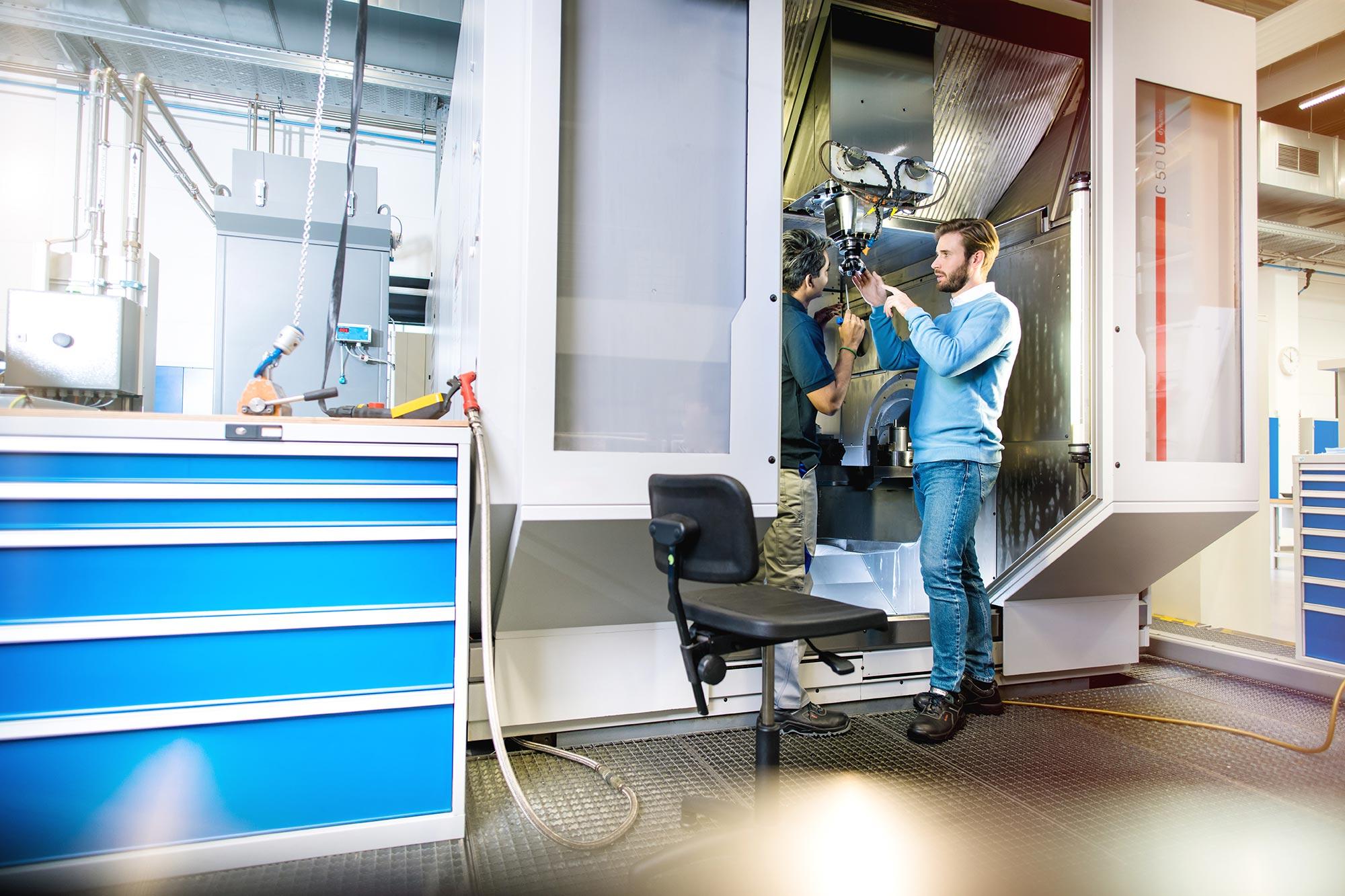 SECO-TOOLS-Global Communication Mitarbeiter der Produktion und Kunde sprechen konzentriert mit Werkzeug vor der CNC Maschine