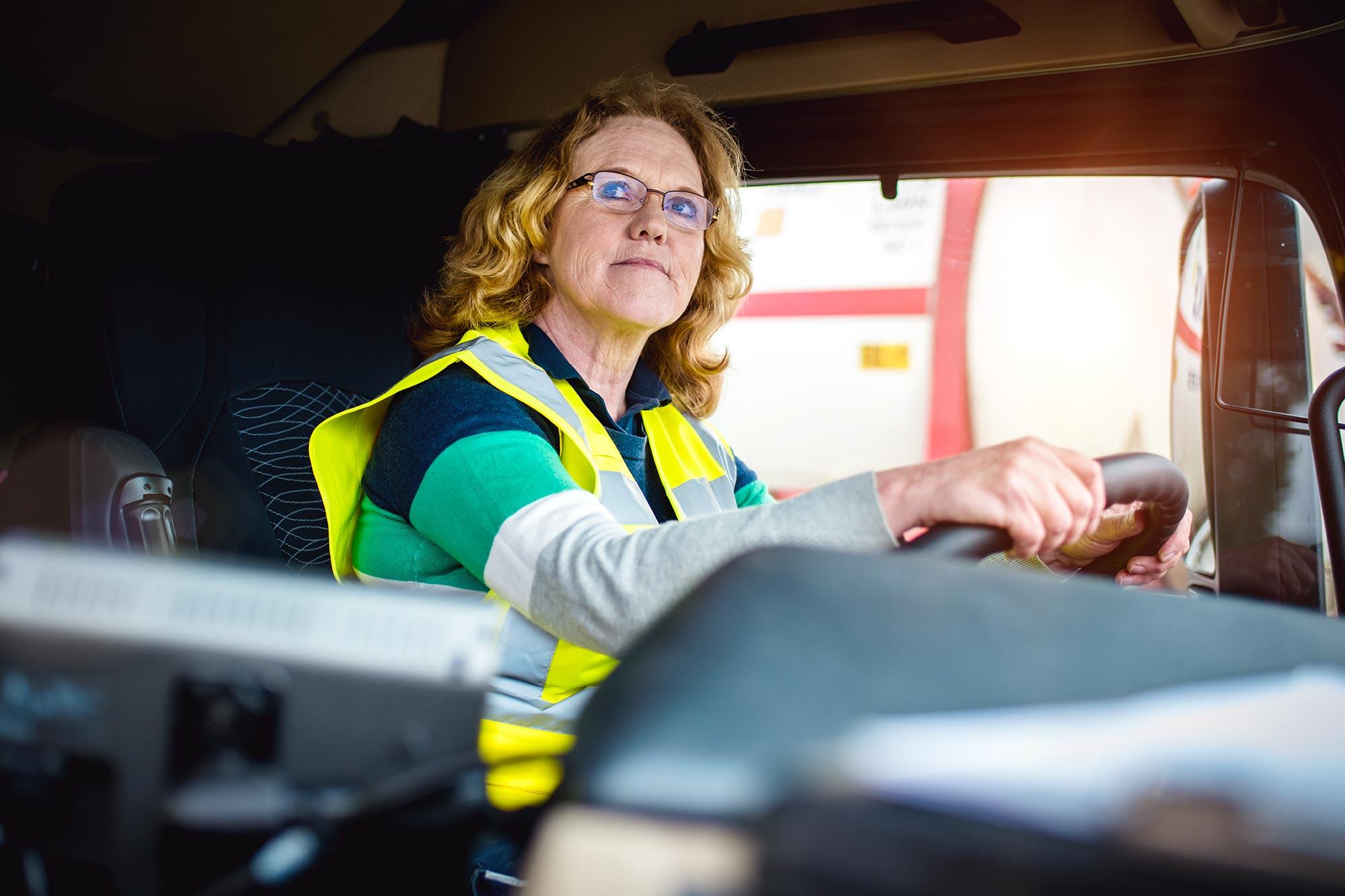Talke Logistics Mitarbeiter Motive LKW Fahrerin in der Kabine eines Lastwagens zuversichtlich entschlossen professionell Truckerin Frau