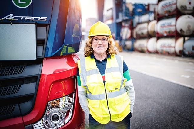 Talke Logistics Mitarbeiter Motive LKW Fahrerin vor ihrem Truck freundlich zuversichtlich professionell Truckerin