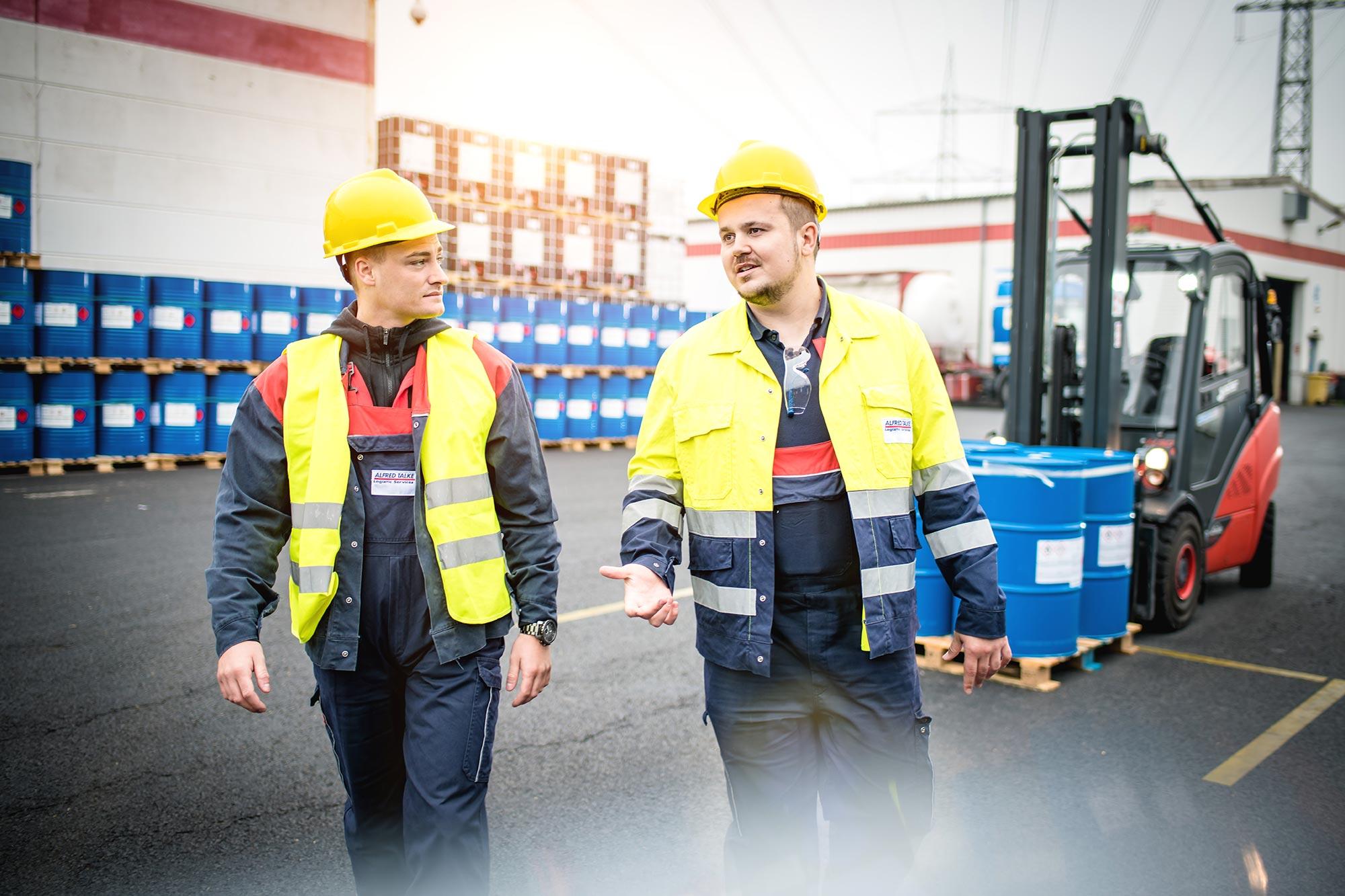 Talke Logistics Mitarbeiter Motive Logistik Arbeiter auf dem Betriebshof laufen reden mit Gabelstabler