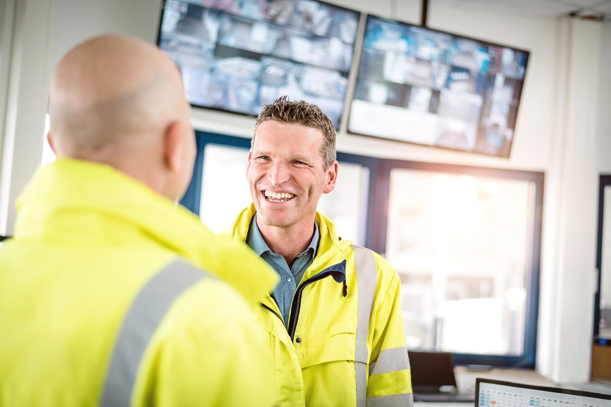 Talke Logistics Mitarbeiter Motive Sicherheitsleute im Gespräch in Kontrollraum auf Betriebshof lachend freundlich professionell
