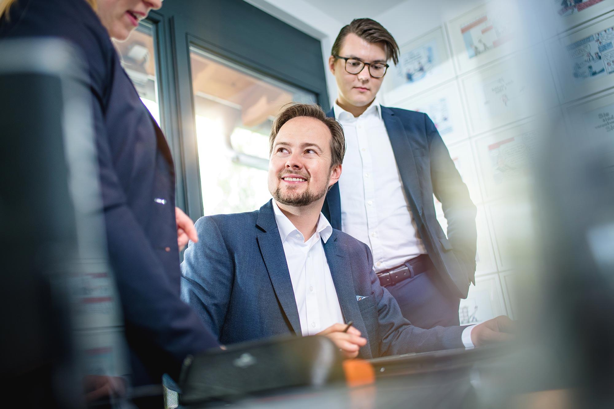 Santiago Advisors Beratungsagentur Imagemotive Businessfotografie Besprechung am Arbitsplatz Men in Suits