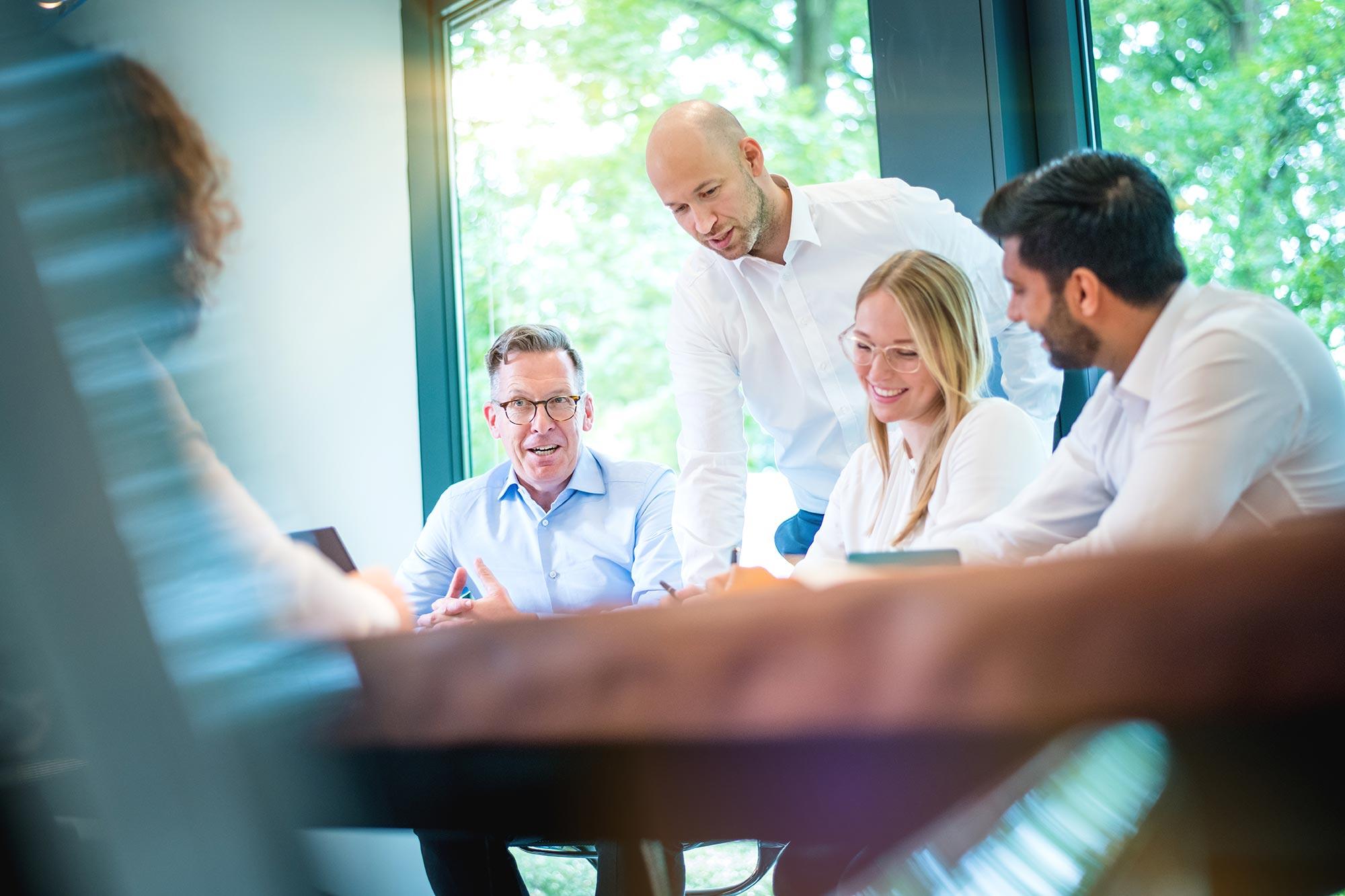 Santiago Advisors Beratungsagentur Imagemotive Businessfotografie Meetingraum Gruppen am Tisch bei Besprechung motiviert konzentriert