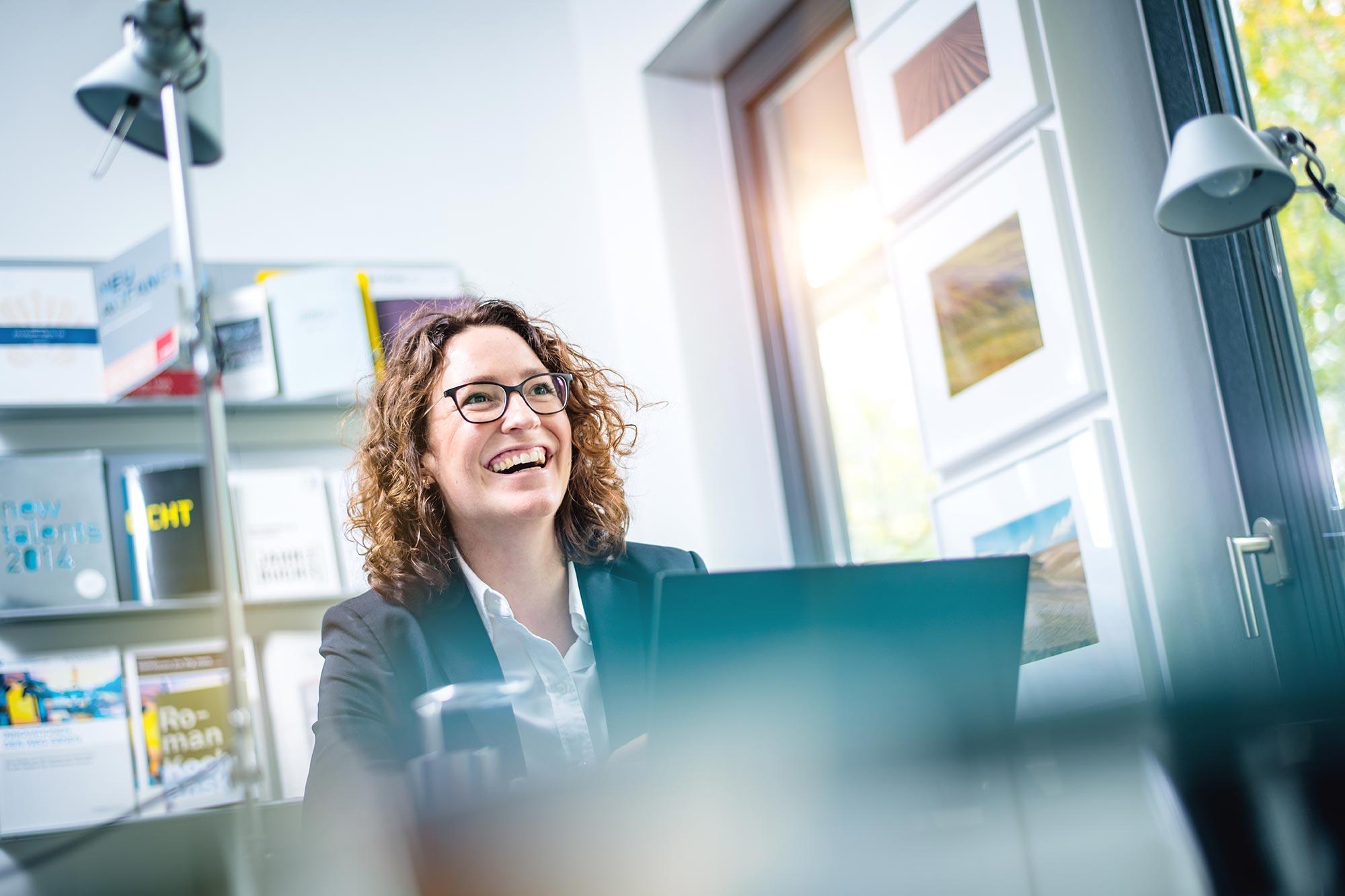 Santiago Advisors Beratungsagentur Imagemotive Businessfotografie Mitarbeiterin hoch motiviert am Arbeitsplatz lachend froh modern